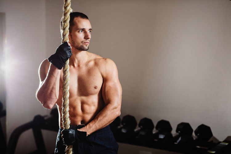 Shirtless Muscular Man Holding Rope While Standing In Gym