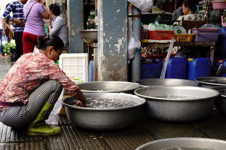 Woman crouching by container with water at market