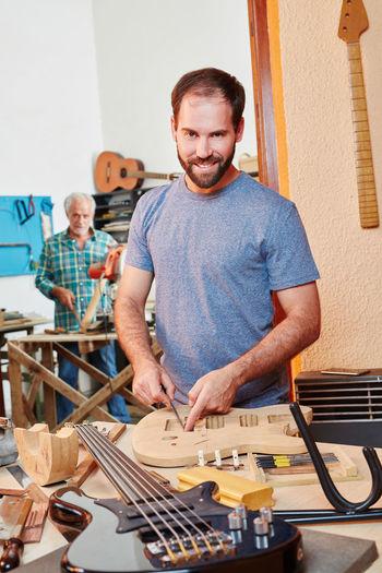 Portrait of smiling carpenters standing at workshop