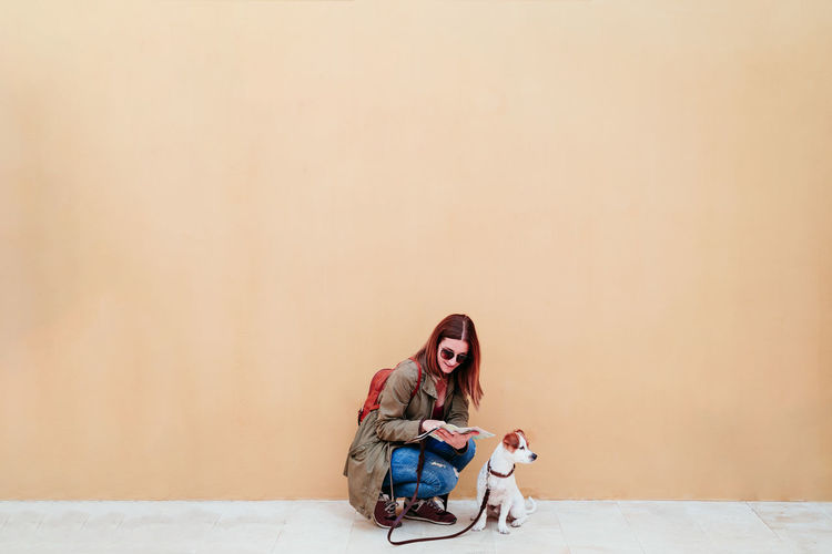 Woman with dog sitting against wall