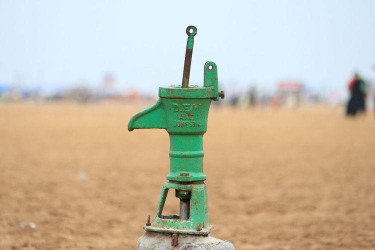 Green water pump on field against sky