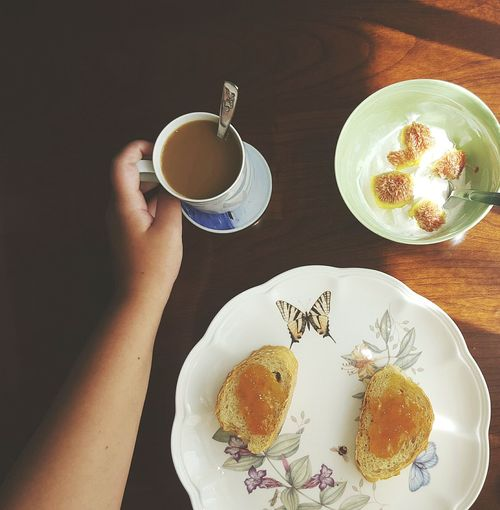 Cropped Hand Holding Tea Cup By Bread In Plate On Table
