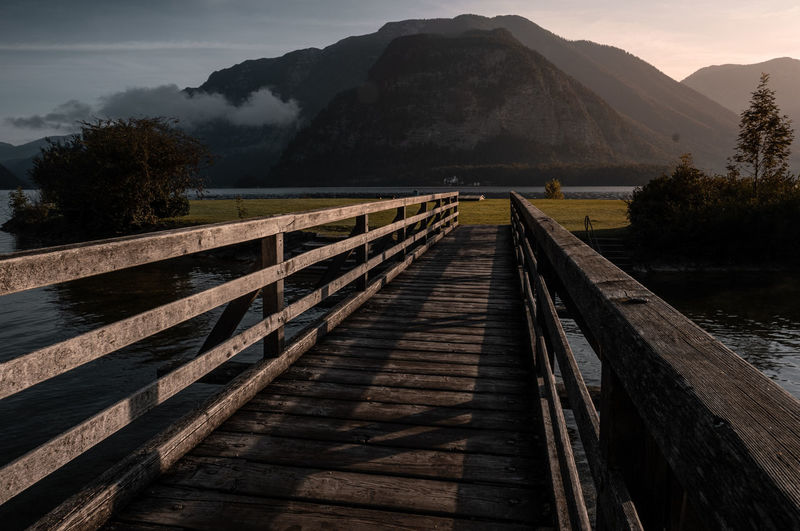 Wooden footbridge over river leading towards mountains against sky