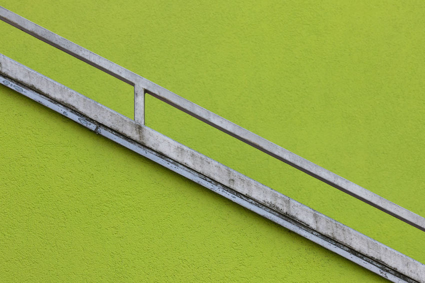 Close-up of a staircase railing against a lime green wall Architectural Feature Architecture Bannister Close-up Copy Space Day Dividing Line Focus On Foreground Full Frame Geometry Green Color Metal Metallic No People Outdoors Railing Side View Single Object Slanted Steps And Staircases Striped Tilt Two Tone - Color Vibrant Color Wall - Building Feature The Architect - 2017 EyeEm Awards