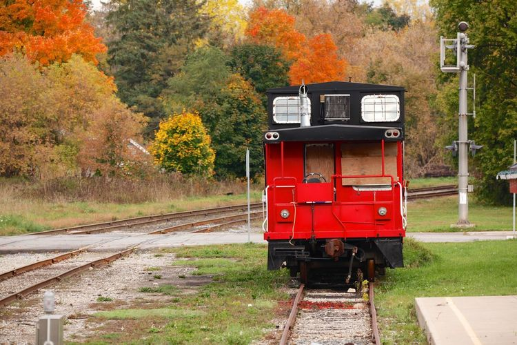 Red Railroad Car On Tracks During Autumn