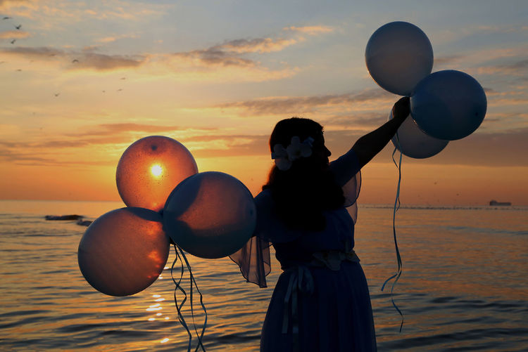 Silhouette woman holding balloons while standing at beach against sky during sunset