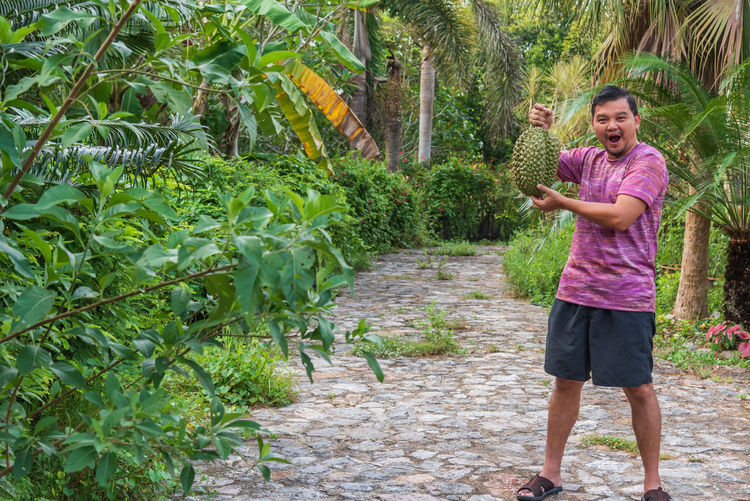 Portrait of shocked mature man holding durian while standing on footpath amidst plants