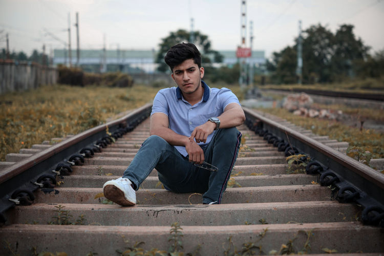 Portrait of young man sitting on railroad track