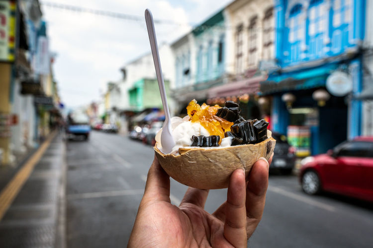 City Street Transportation Architecture Mode Of Transportation Holding Food And Drink Food One Person Human Hand Focus On Foreground Building Exterior Hand Built Structure Motor Vehicle Incidental People Day Car Human Body Part Freshness Outdoors Temptation Ice Cream Coconut Coconut Shell