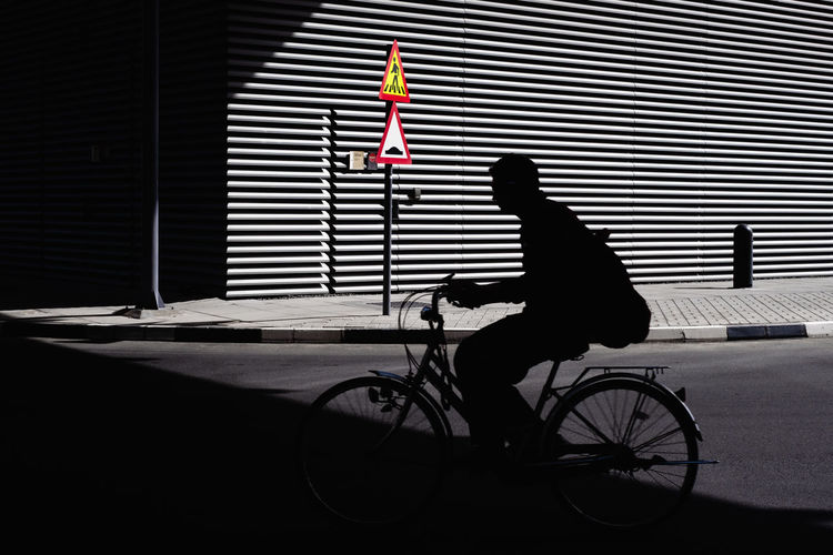 Side view of silhouette man riding bicycle on road