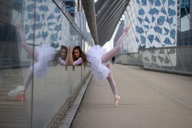 Full length of woman dancing on bridge