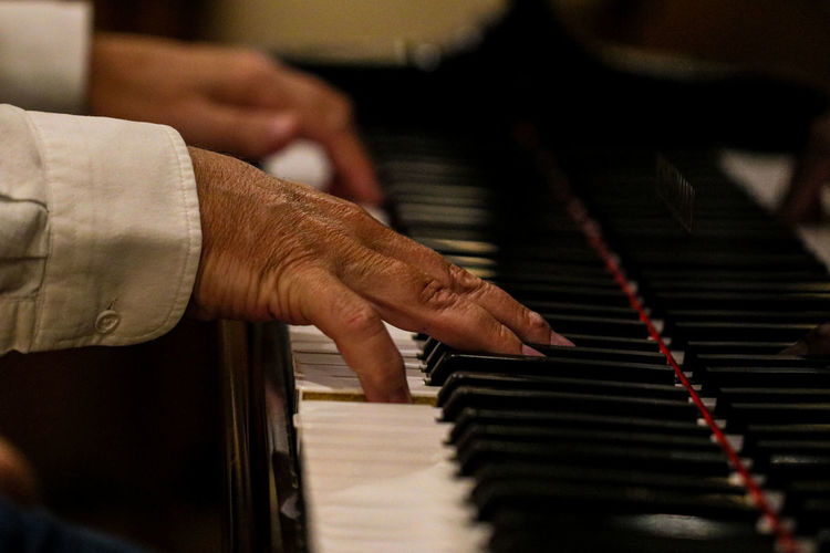 Cropped hands of man playing piano