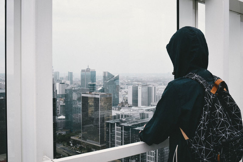 Rear view of man looking at cityscape through window