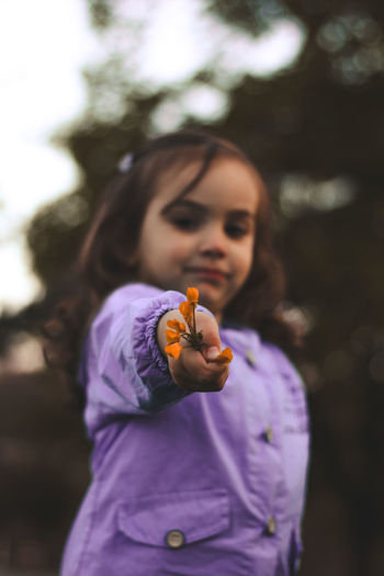 Low Angle Portrait Of Cute Girl Holding Flowers While Standing In Park During Sunset