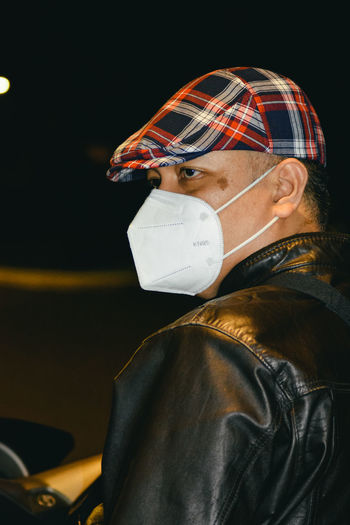 Close-up side view portrait of a masked man sitting on a motorcycle on the street at night