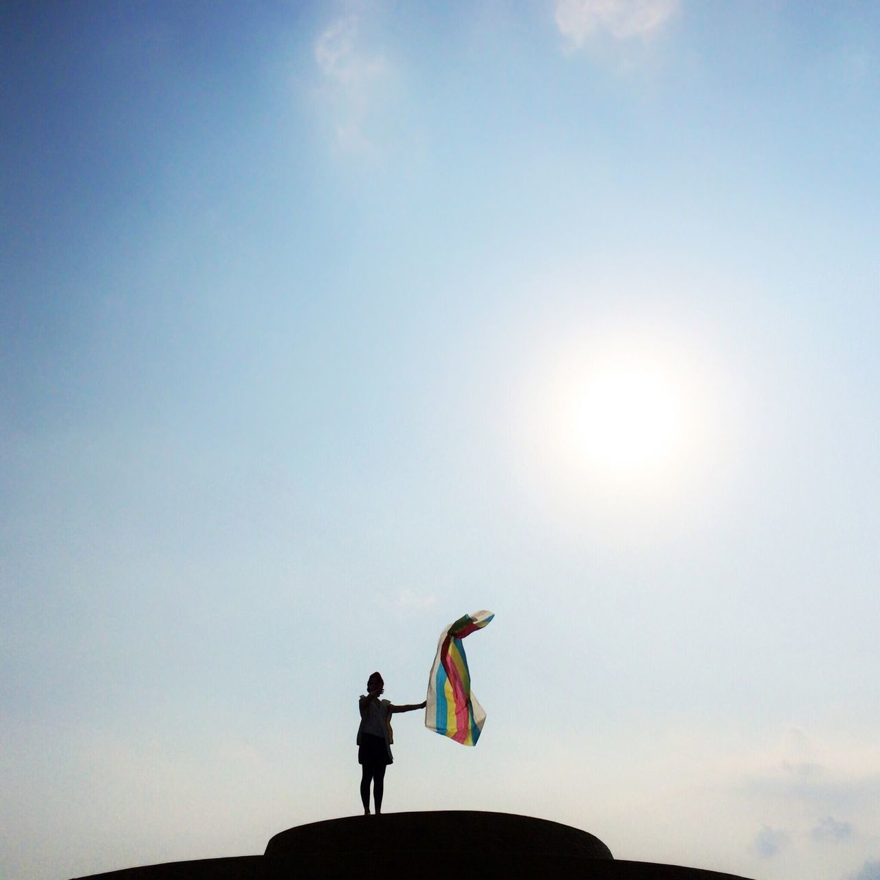 Low angle view of silhouette woman with colorful cloth against sky
