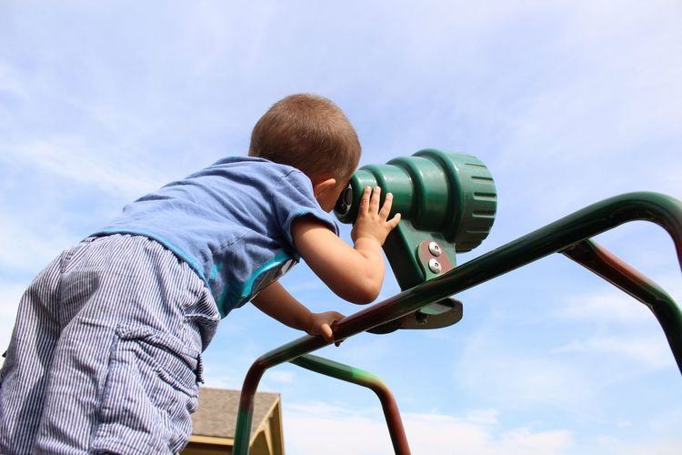 Low angle view of boy looking through hand-held telescope against sky