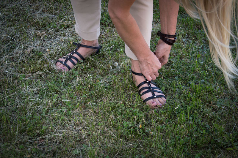 Low section of woman wearing sandal on grass