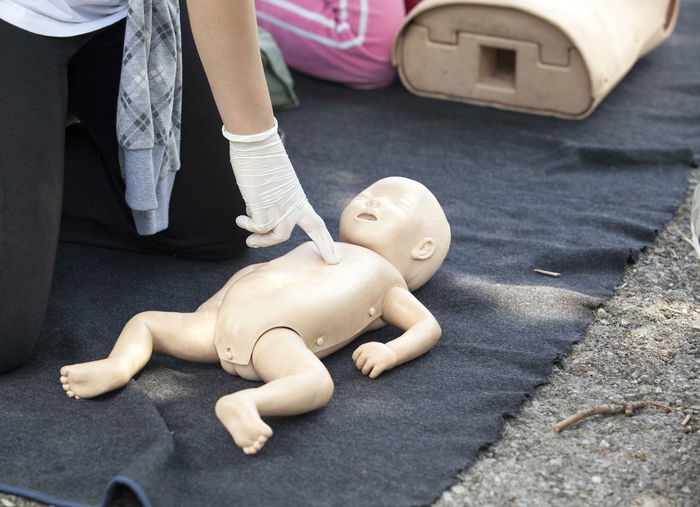 Midsection of paramedics performing cpr on baby mannequin