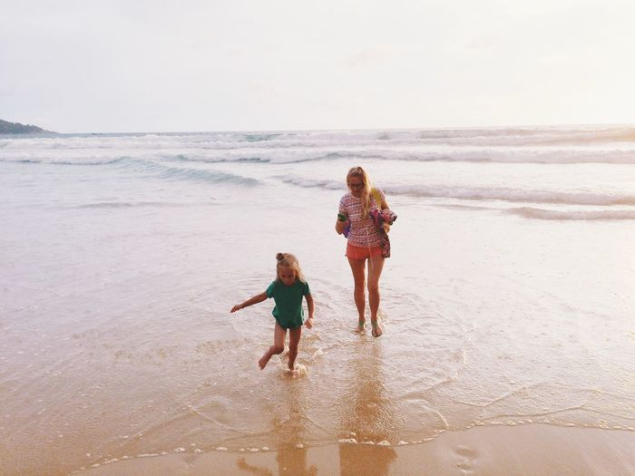 Full Length Of Mother And Daughter Walking On Shore At Beach