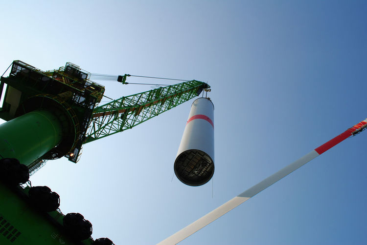 Low angle view of crane lifting column