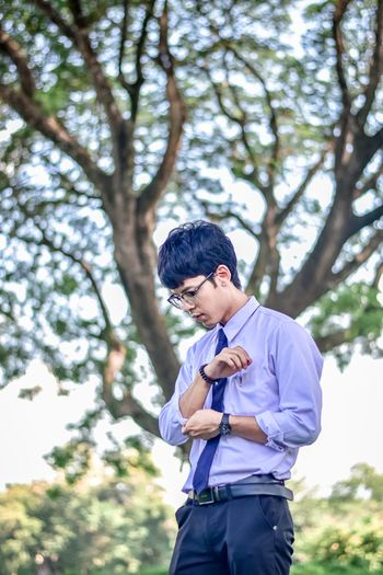 Young man adjusting sleeve while standing against trees