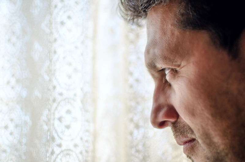 Close-up of thoughtful man looking away by curtain