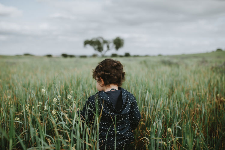 Rear view of girl standing by plants against sky