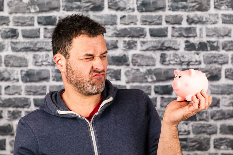 Man making face while holding piggy bank against wall