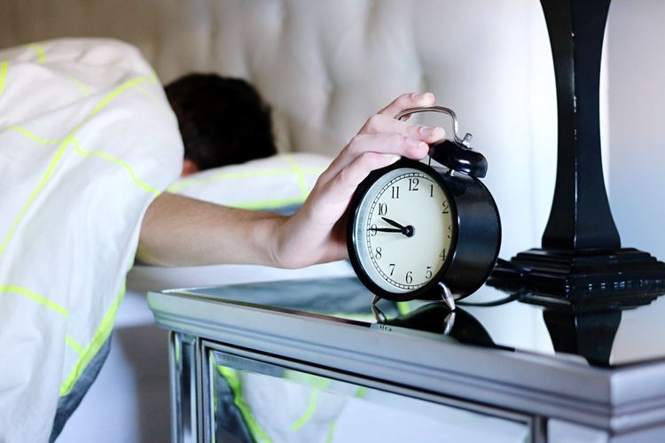 Close-up of man touching alarm clock while sleeping on bed at home