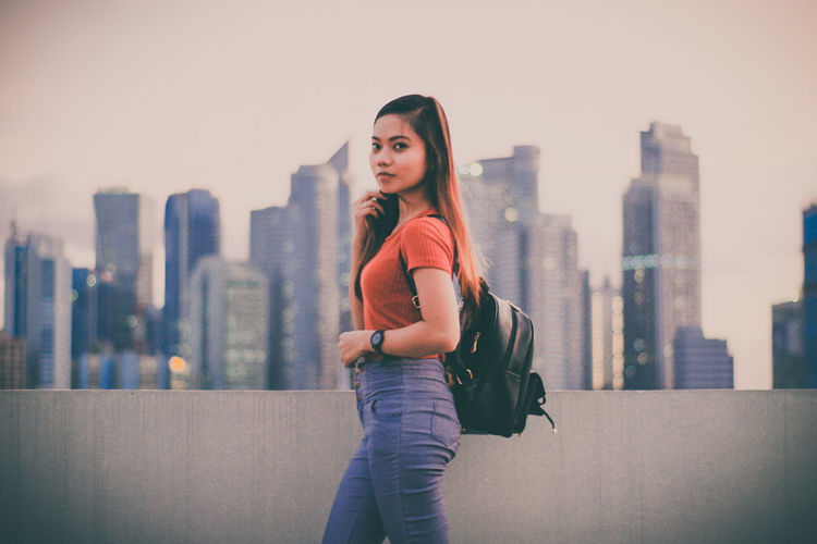 Portrait of young woman standing on roof against cityscape