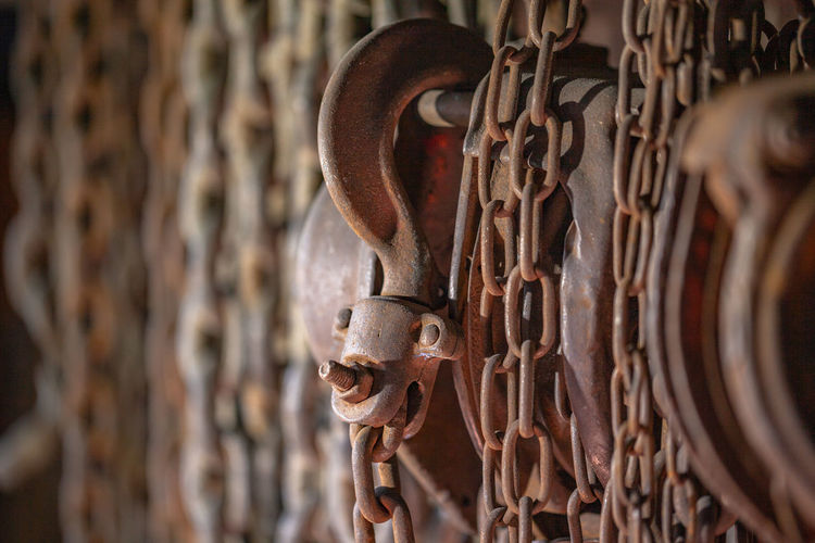 Close-up of rusty chain hanging on metal gate