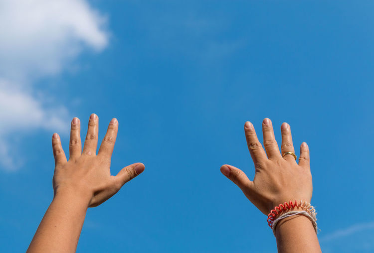 Cropped hands of people against blue sky