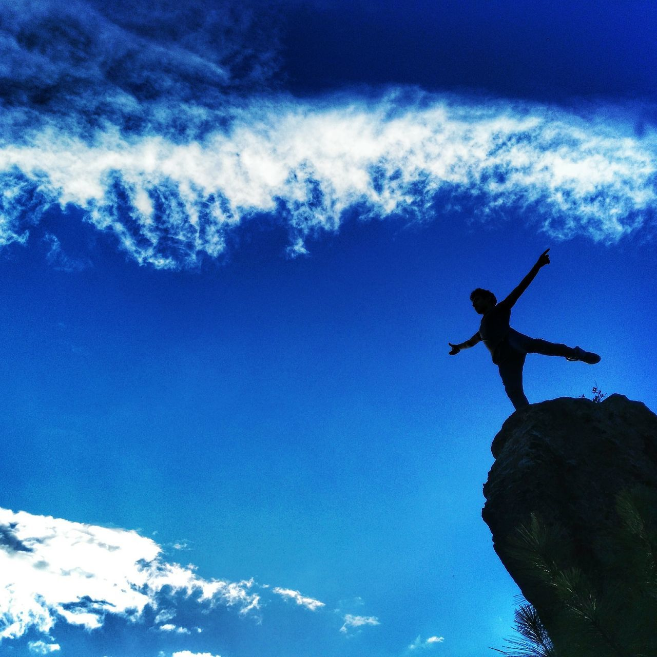 sky, low angle view, one person, cloud - sky, silhouette, full length, day, outdoors, real people, men, adventure, leisure activity, mid-air, blue, lifestyles, nature, climbing, energetic, extreme sports, people