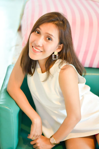 Portrait of smiling beautiful woman sitting on sofa