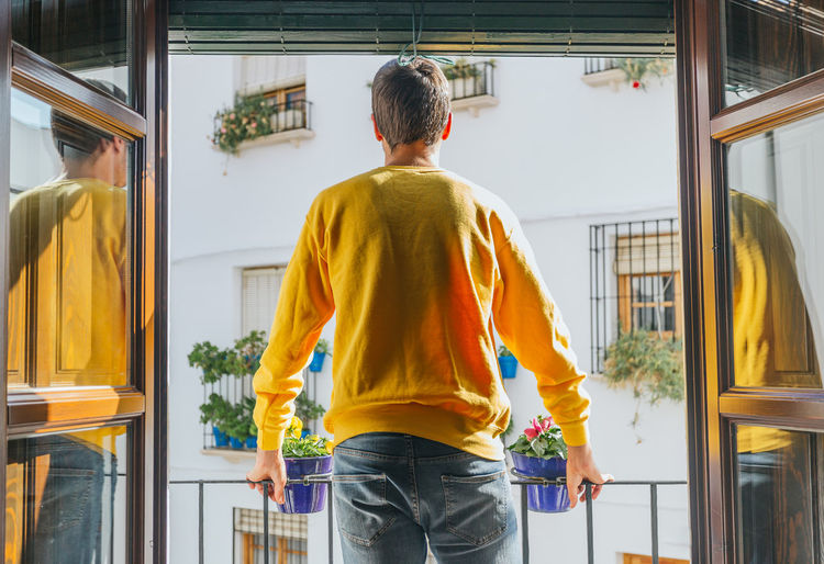 Rear view of man standing by window