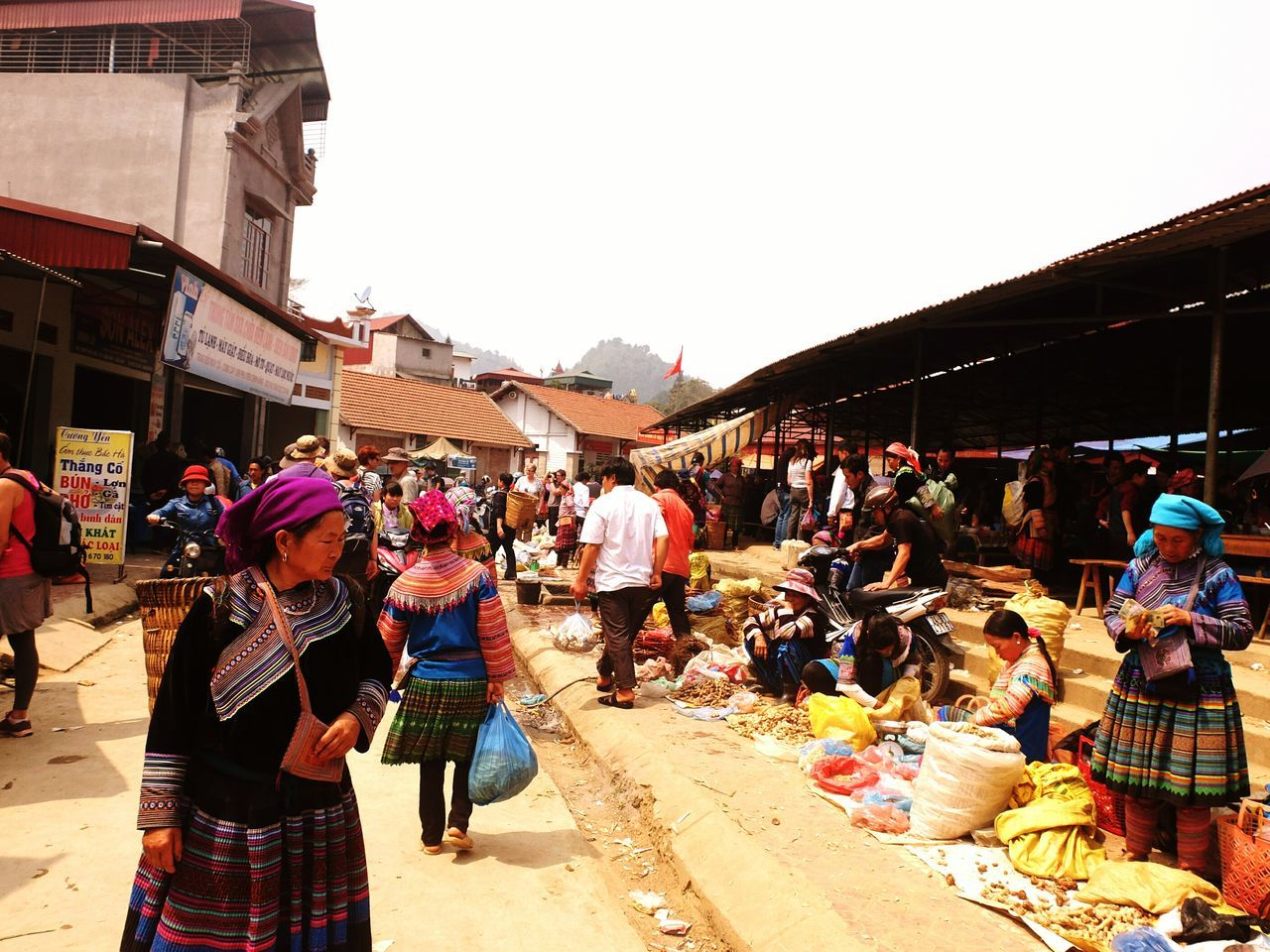 large group of people, real people, market, men, market stall, retail, market vendor, women, built structure, small business, building exterior, outdoors, architecture, day, lifestyles, clear sky, farmer market, group of people, food, crowd, freshness, city, sky, adult, people