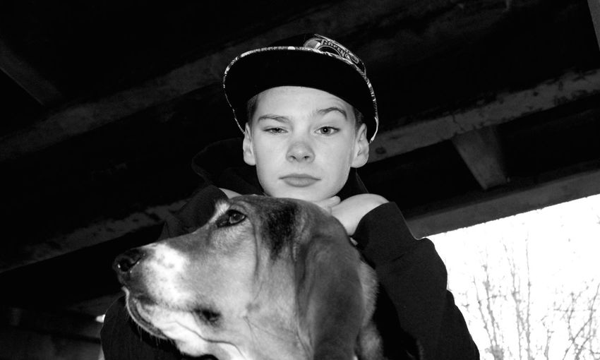 Portrait Of Boy Wearing Cap By Dog Against Roof
