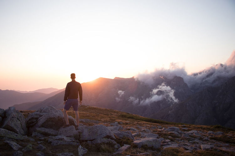 Rear view of man standing on mountain against sky during sunset