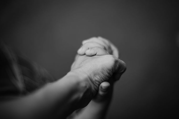 Cropped image of friends holding hands