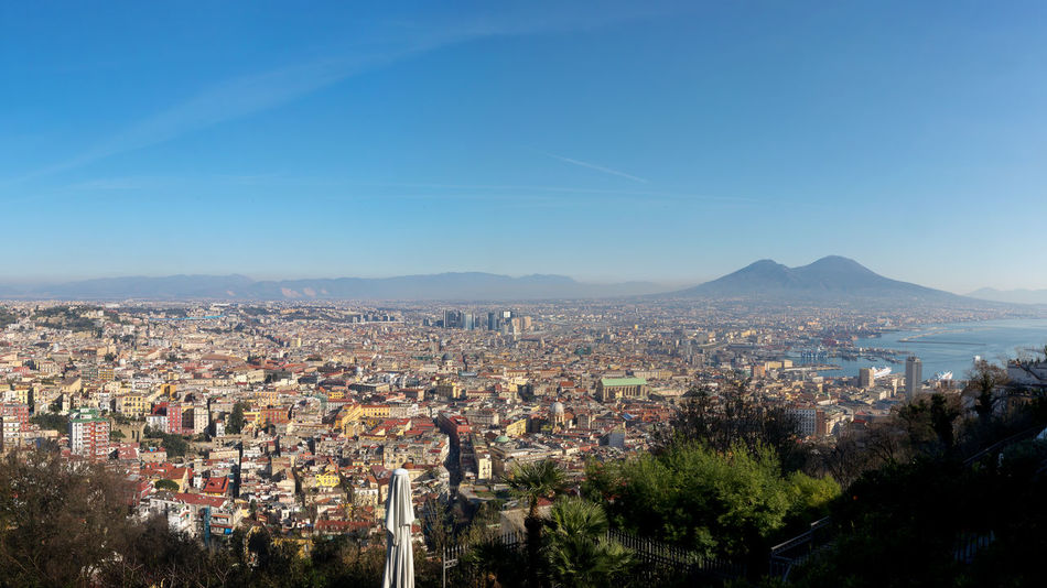 Panoramic view of the city of Naples, and in the background the volcano Vesuvius. Building Exterior Sky Architecture Cityscape City Built Structure Mountain Tree Nature No People Residential District Building Plant Blue Outdoors Day High Angle View Clear Sky TOWNSCAPE Naples, Italy Landscape Cityscape Vesuvius  City