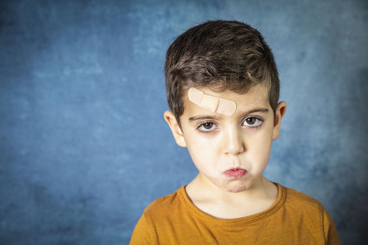 Kid with a band aid Band Aid Sad Portrait Headshot Childhood Looking At Camera Front View One Person Indoors  Child Males  Boys Casual Clothing Men Wall - Building Feature Real People Lifestyles Offspring Standing Innocence Making A Face Human Face Blue Background Contemplation