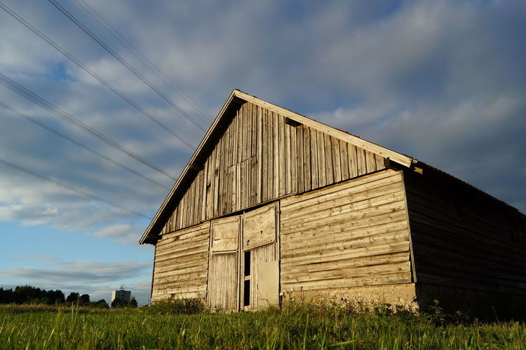 Abandoned barn on field against sky