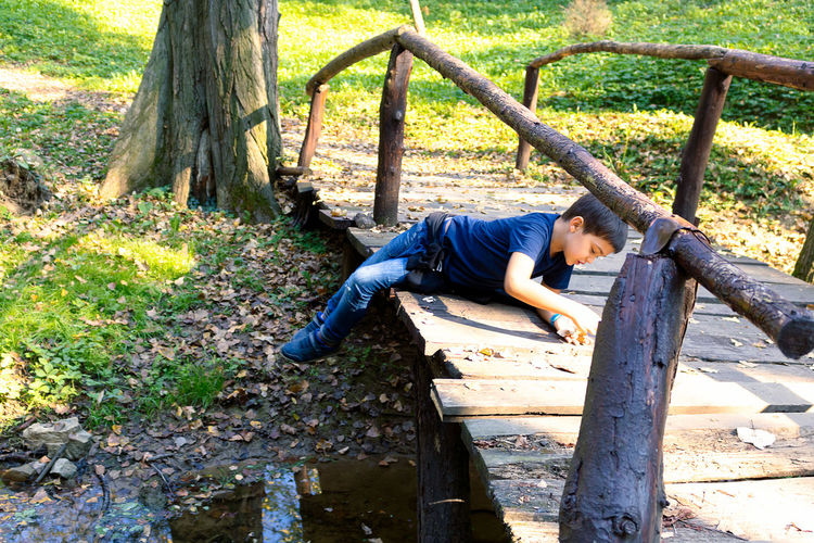 High angle view of man relaxing on tree trunk