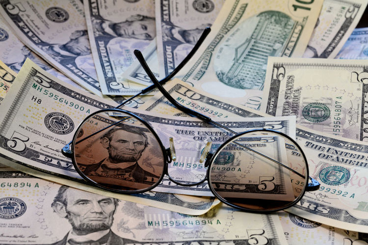 Sunglasses is placed on the banknote of US dollars spread around Dollar Money Cash Savings Banking Finance Bill Currency Wealth Background Banknote Bussiness Profit Green Close-up USD Exchange Loan  Paper Sign Payment Pay Stack Number Textured  Abstract Earnings Symbol Capital Assets Sunglasses Face President Business Paper Currency Investment No People Human Representation Backgrounds Corporate Business Full Frame Representation Large Group Of Objects Studio Shot Exchange Rate Economy Making Money Bank