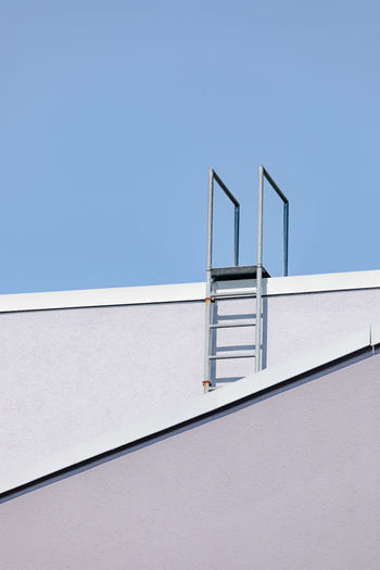 Low Angle View Of Ladder On Wall Against Clear Sky