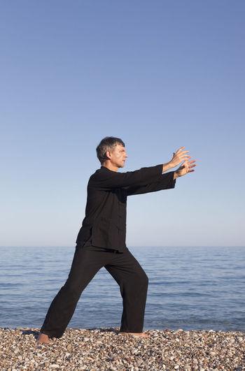 Full length of man doing martial arts at beach