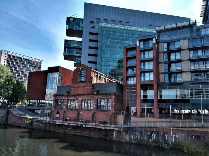The old pump house on the banks of the River Irwell, Manchester UK with the new construction of the glass Civil Justice Centre directly behind it and Albert Bridge House in the background. Architecture Built Structure Building Exterior Water City Building Waterfront Sky Nature Day No People River Window Modern Reflection Outdoors Residential District Glass - Material Office Building Exterior Manchester UK River Irwell Pump House