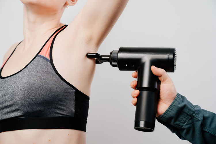 Cropped hand massaging woman with massager against gray background