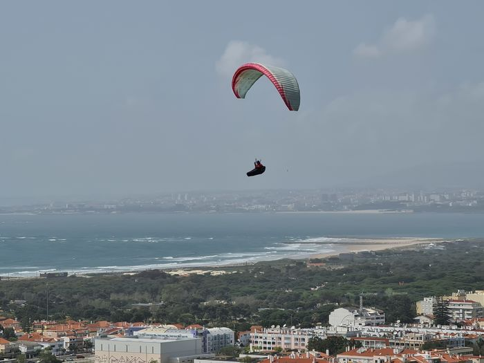 People paragliding over sea by city against sky